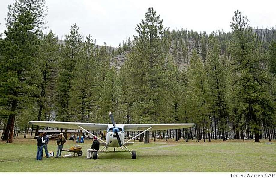 In this  April 15, 2009 photo,  Ray Arnold sits on the wheel of the Cessna 185 airplane he uses to deliver mail and other supplies to the remote Idaho backcountry, as he visits with Greg Metz and Sue Anderson, caretakers of the Yellow Pine Bar property near the Salmon River in central Idaho's Frank Church-River of No Return Wilderness. Arnold flies the only backcountry air mail route left in the lower 48 states, delivering mail to nearly two dozen ranches on a stretch of land larger than Indiana. (AP Photo/Ted S. Warren) Photo: Ted S. Warren, AP