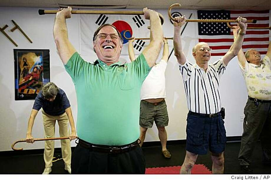 Robert St. John, Jr., left, of Valrico, Fla., Ed Smoak of Pinellas Park, Fla. and Ajmal Khan of Plant City, Fla. do stretching exercises with their canes while Grand Master Mark Shuey teaches a self-defense seminar on Cane-Fu, defending yourself with a simple walking cane, at the Gary Hernandez Martial Arts studio on Sunday, Feb. 15, 2009 in Zephyrills, Fla. (AP Photo/Craig Litten) Photo: Craig Litten, AP