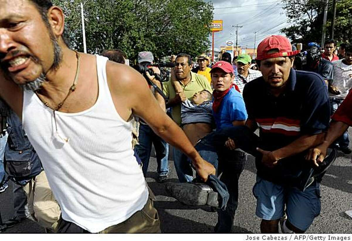 Supporters of Honduran President Manuel Zelaya carry the dead body of a man after he was shot by Honduran soldiers outside Toncontin international airport in Tegucigalpa on July 5, 2009. Ousted President Manuel Zelaya reaffirmed his intention to return to Honduras on Sunday, despite a threat by the interim government that it will bar his plane from landing in the country. AFP PHOTO/ Jose Cabezas (Photo credit should read Jose CABEZAS/AFP/Getty Images)
