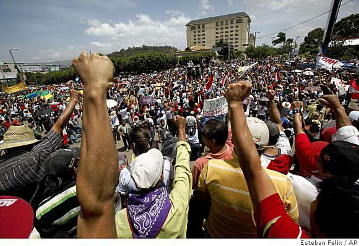 Supporters of ousted Honduras President Manuel Zelaya protest near the presidential residence in Tegucigalpa, Saturday July 4, 2009. Honduras rebuffed demands by the international community to reinstate President Zelaya and pulled out of the Organization of American States, thrusting the poor Central American nation deeper into political crisis and isolation. (AP Photo/Esteban Felix)
