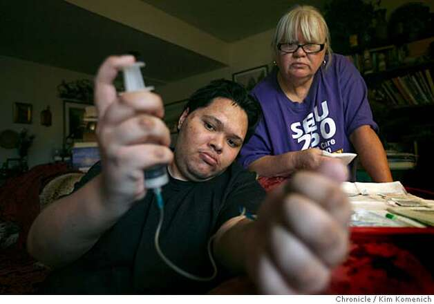 Ernie Campbell self-administers a dose of Factor VII hempophilia medicine in his Novato, Ca. home on Feb. 23, 2008 as his mother Dianne Campbell watches. Ernie relies on a constant supply of extremely expensive medicine provided by state medical agencies to keep his hemophilia in check. Gov. Schwarzenegger has proposed a plan that would require Campbell and other Californians with chronic conditions to submit paperwork to the state twice as often. Campbell says the increased bureaucracy will create a greater possibility that a lost or delayed form will put him in a life-threatening situation  Photo by Kim Komenich / San Francisco Chronicle Photo: KIM KOMENICH