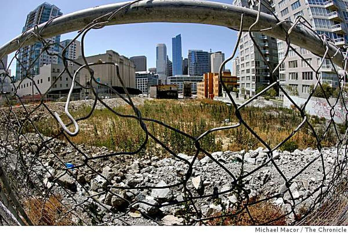 The vacant lot sits idle behind a chain link fence on the North East corner of Harrison and Folsom Streets on, Saturday June 27, 2009, in San Francisco, Calif., while developers decides how to fill the empty spaces before construction begins.