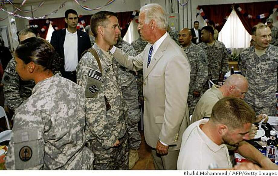 **RETRANSMITTED WITH ALTERNATE CROP** U.S. Vice President Joe Biden (R) talks with his son, U.S. Army Capt. Beau Biden (L) at Camp Victory on the outskirts of Baghdad on July 4, 2009.  Biden said that America's role in Iraq was switching from deep military engagement to one of diplomatic support, ahead of a complete withdrawal from the country in 2011. AFP Photo/ Khalid Mohammed-POOL (Photo credit should read KHALID MOHAMMED/AFP/Getty Images) Photo: Khalid Mohammed, AFP/Getty Images
