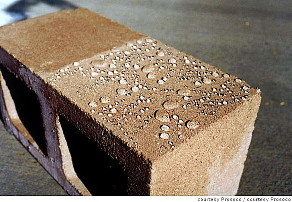A concrete block, half sealed. The unsealed side is darkend by water. The sealed side shows water beaded on the surface. the color is unchanged because a penetrating sealer was used.