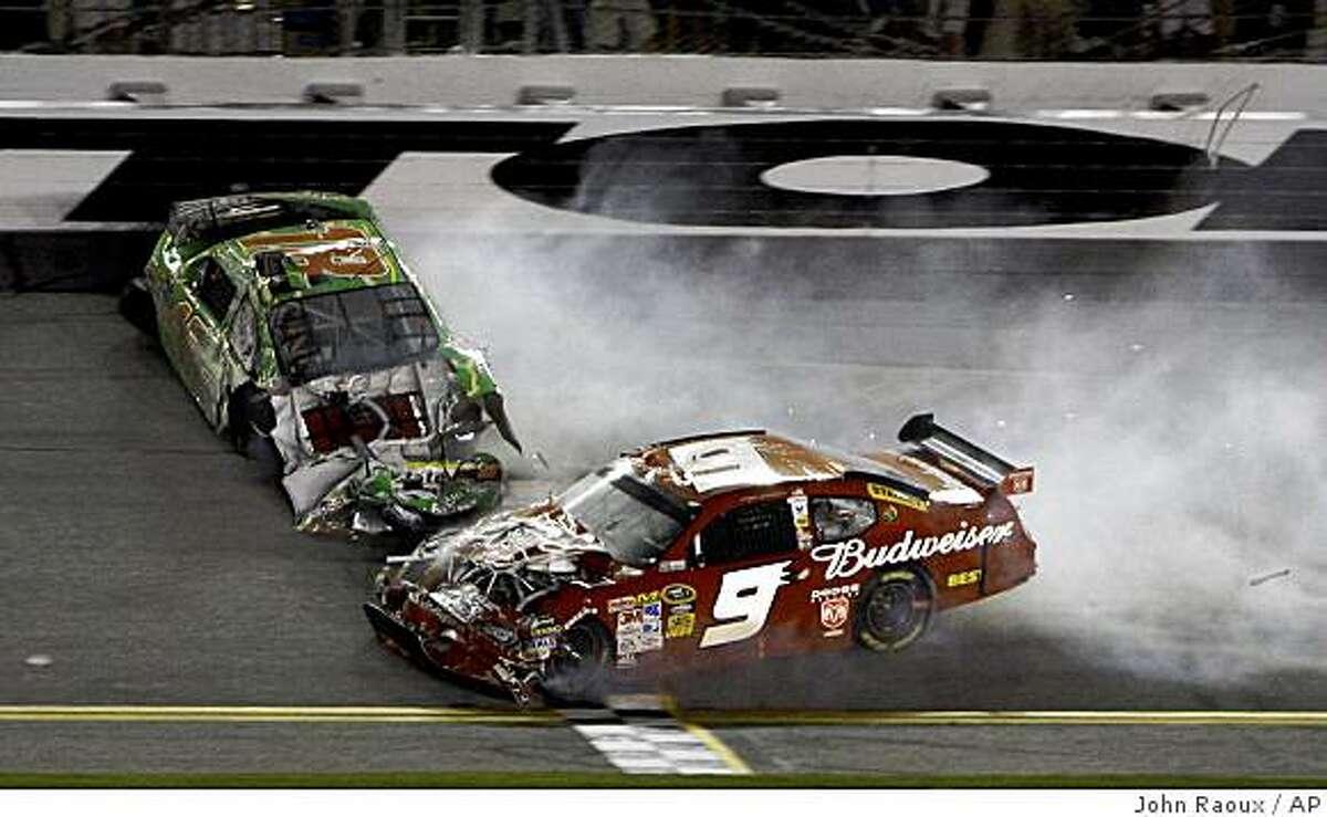 Kyle Busch (18) and Kasey Kahne (9) slide across the finish line after they were involved in a crash on the last lap of the NASCAR Coke Zero 400 auto race at Daytona International Speedway in Daytona Beach, Fla., Saturday, July 4, 2009. (AP Photo/John Raoux)