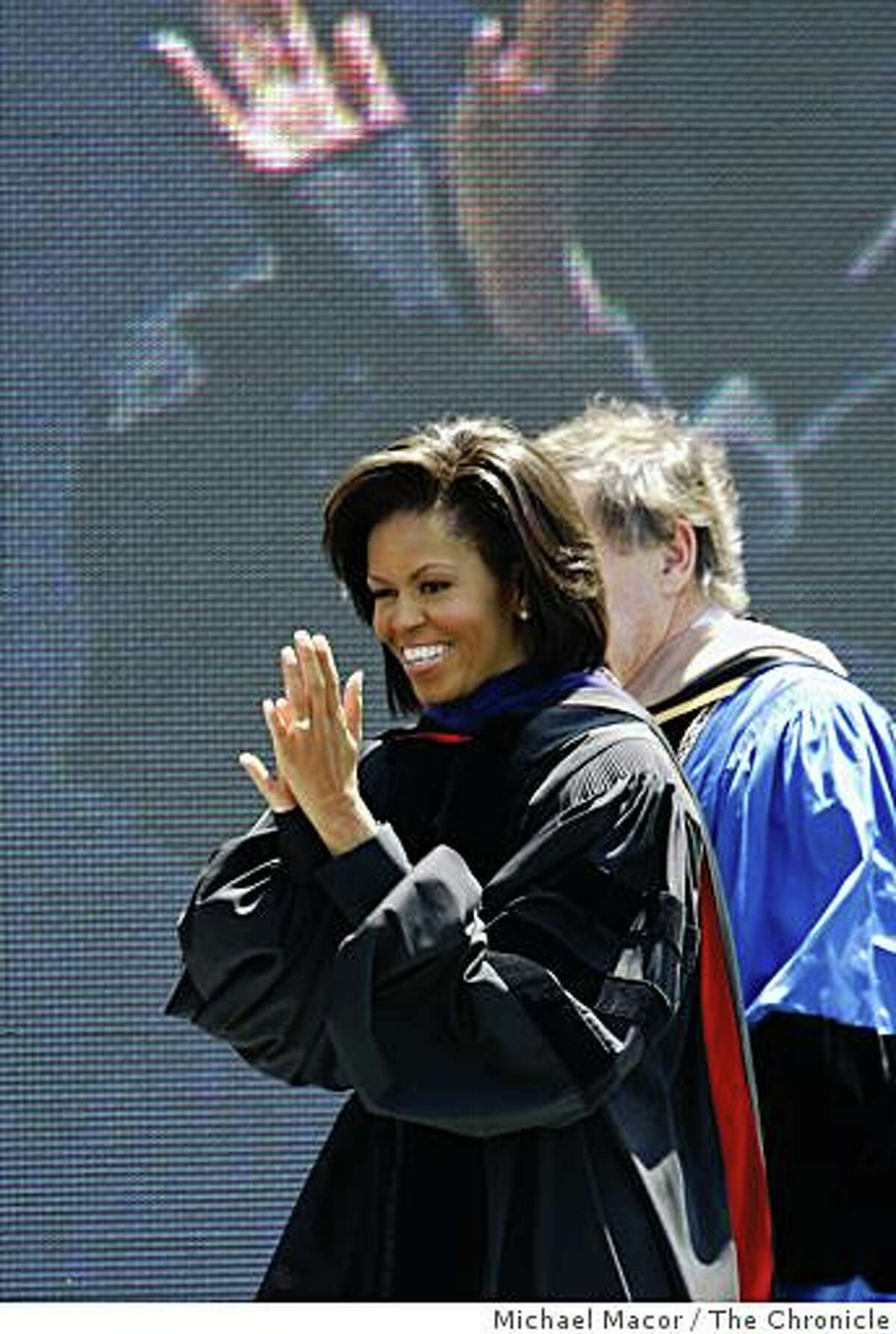 First Lady Michelle Obama, claps to the graduatuing upon entering the stage, moments before she delivers the commencement speech to the first full graduating class of UC Merced on Saturday, May 16, 2009 in Merced, Calif.
