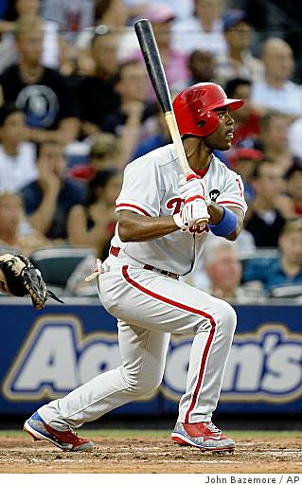 Philadelphia Phillies' Jimmy Rollins follows through with a base hit in the fourth inning of a baseball game against the Atlanta Braves in Atlanta, Thursday, July 2, 2009. (AP Photo/John Bazemore)