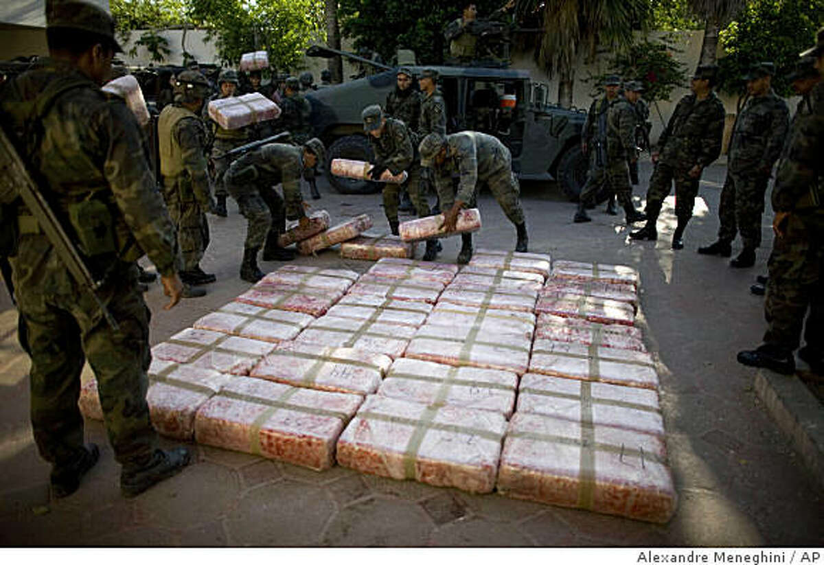 FILE - In this March 20, 2009 file photo, Mexican soldiers lay out packages containing marijuana seized during an anti-drug operation at a military base in Guardados de Abajo, on Mexico's northeastern border with the United States. Mexico has deployed thousands of soldiers and federal agents to drug strongholds as part of a nationwide crackdown on drug cartels since President Felipe Calderon took office in 2006. (AP Photo/Alexandre Meneghini, File)