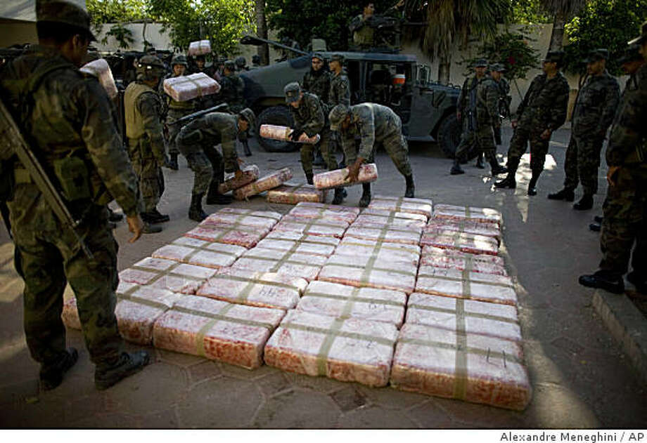 FILE - In this March 20, 2009 file photo,  Mexican soldiers lay out packages containing marijuana seized during an anti-drug operation at a military base in Guardados de Abajo, on Mexico's northeastern border with the United States. Mexico has deployed thousands of soldiers and federal agents to drug strongholds as part of a nationwide crackdown on drug cartels since President Felipe Calderon took office in 2006. (AP Photo/Alexandre Meneghini, File) Photo: Alexandre Meneghini, AP