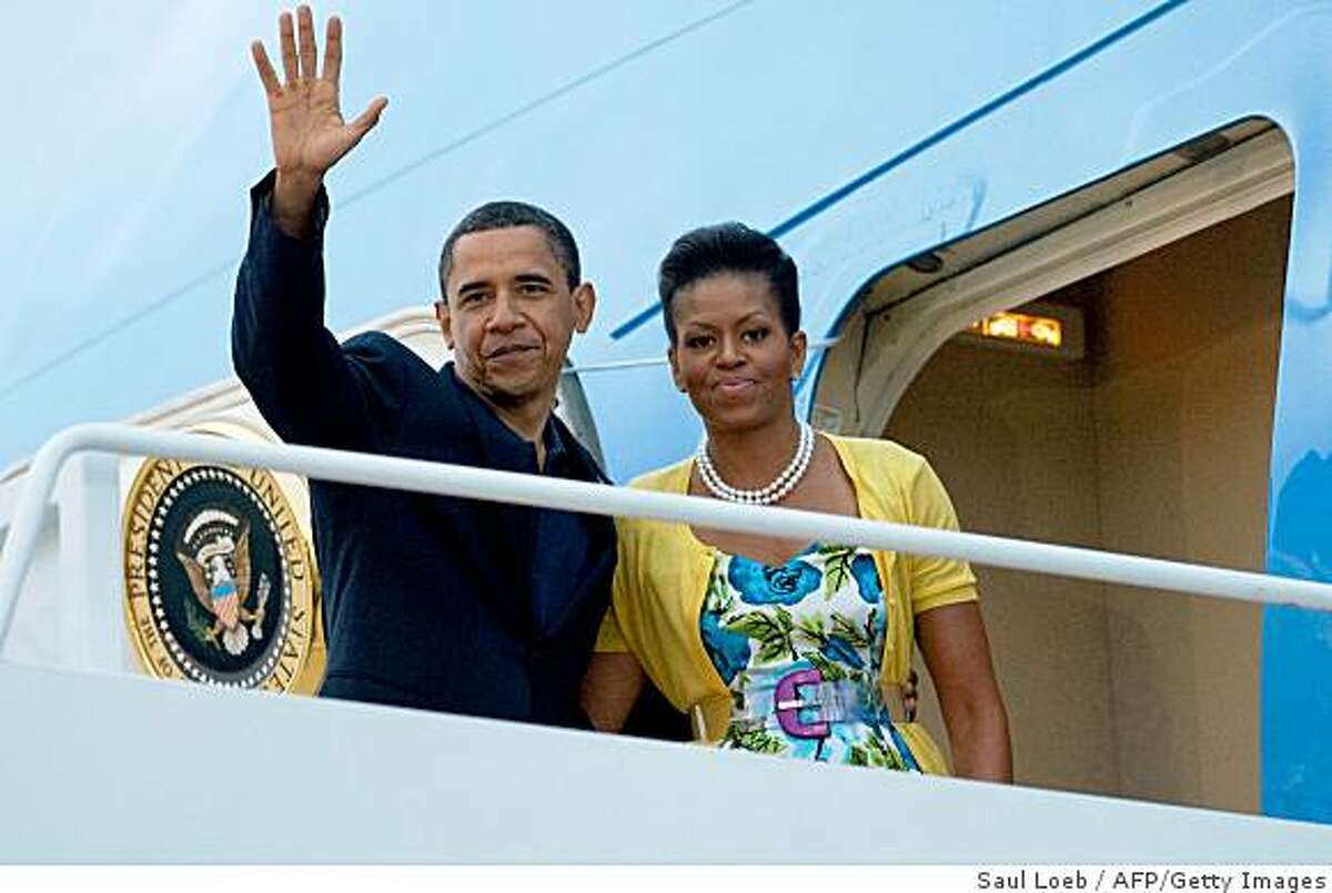 US President Barack Obama waves alongside First Lady Michelle Obama from the steps of Air Force One prior to departing from Andrews Air Force Base in Maryland, July 5, 2009. Obama is traveling to Moscow, Russia, on the first leg of a week-long trip that will also take him to Italy and Ghana. AFP PHOTO / Saul LOEB (Photo credit should read SAUL LOEB/AFP/Getty Images)