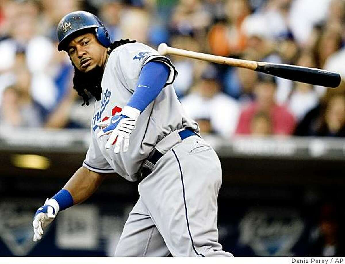 Los Angeles Dodgers' Manny Ramirez tosses his bat after walking during the first inning of a baseball game against the San Diego Padres Friday, July 3, 2009 in San Diego. (AP Photo/Denis Poroy)