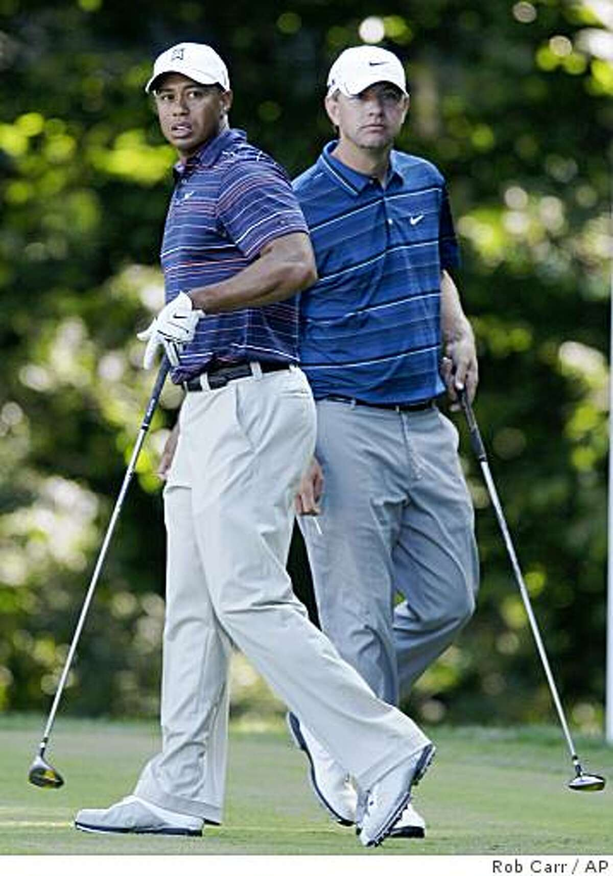 Tiger Woods, left, and Lucas Glover, right, follow Woods' tee shot on the 14th hole during the second round of the AT&T National golf tournament at Congressional Country Club, Friday, July 3, 2009, in Bethesda, Md. (AP Photo/Rob Carr)