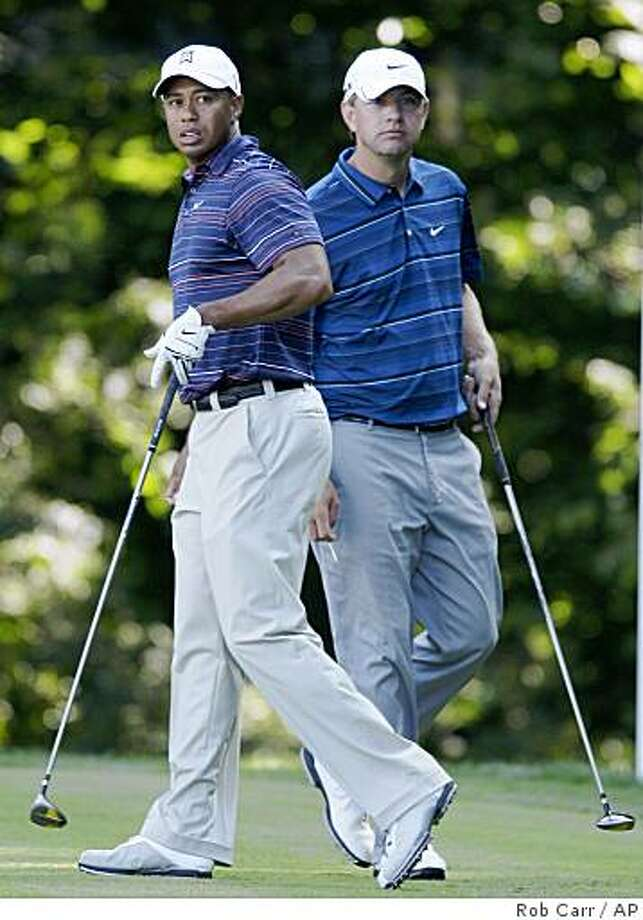 Tiger Woods, left, and Lucas Glover, right, follow Woods' tee shot on the 14th hole during the second round of the AT&T National golf tournament at Congressional Country Club, Friday, July 3, 2009, in Bethesda, Md. (AP Photo/Rob Carr) Photo: Rob Carr, AP