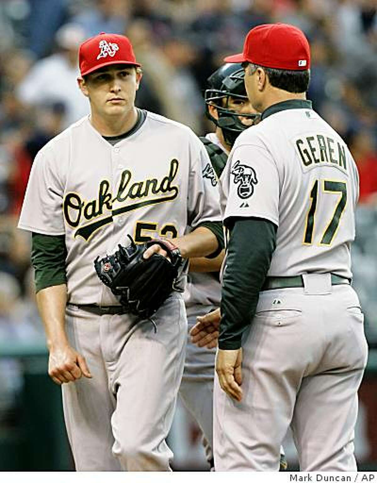 Oakland Athletics pitcher Trevor Cahill, left, leaves the game as manager Bob Geren (17) pulls the starter in the fourth inning of a baseball game Oakland Athletics the Cleveland Indians, Friday, July 3, 2009, in Cleveland. (AP Photo/Mark Duncan)
