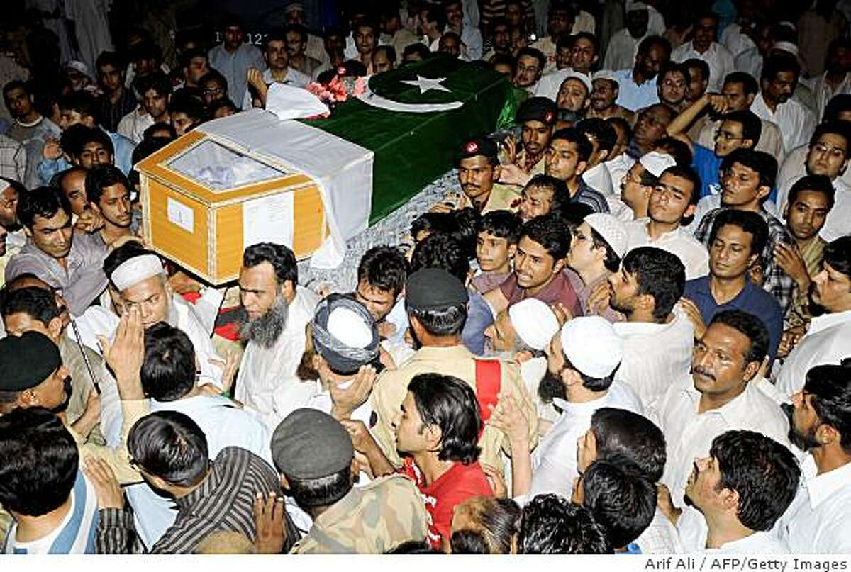 Troops, family members and residents carry the coffin of Pakistan's army Major Hafiz Atiq, who was killed in the ongoing operation against Taliban militants in the troubled Swat region, during his funeral ceremony in Lahore on June 24, 2009. More than 1,500 insurgents and 140 soldiers have been killed in military operations launched in Lower Dir, Buner and in Swat. Pakistani troops are wrapping up an almost two-month-long operation against Taliban rebels in northwest Swat valley, and are preparing to soon launch the second front against Pakistan Taliban chief Baitullah Mehsud and his network along the rugged tribal belt. AFP PHOTO/ARIF ALI (Photo credit should read Arif Ali/AFP/Getty Images)