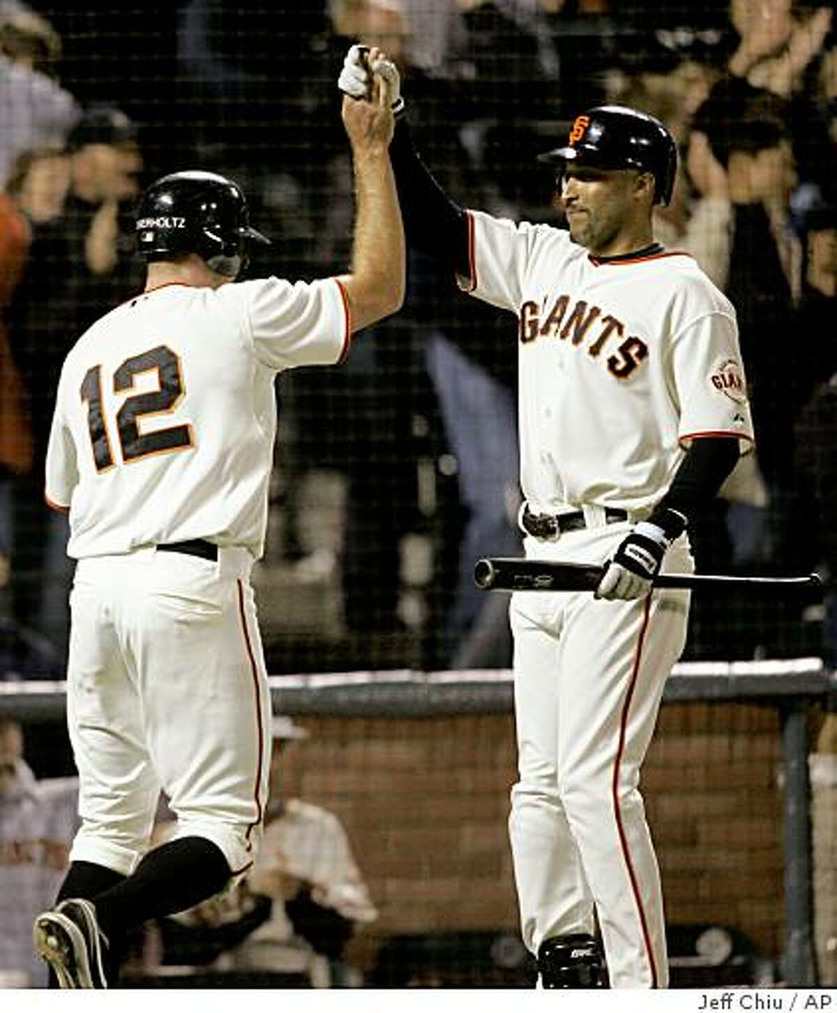 San Francisco Giants' Nate Schierholtz, left, is congratulated by Randy Winn after scoring on a wild pitch from Texas Rangers' Jason Jennings in the 11th inning of a baseball game in San Francisco, Saturday, June 20, 2009. The Giants won 2-1 in 11 innings. (AP Photo/Jeff Chiu)