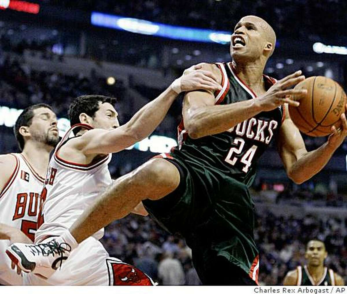 Chicago Bulls guard Kirk Hinrich, left, fouls Milwaukee Bucks forward Richard Jefferson as Jefferson shoots during the first half of their NBA basketball game in Chicago, Friday, March 6, 2009. Watching on the play for the Bulls is Brad Miller, left. (AP Photo/Charles Rex Arbogast)