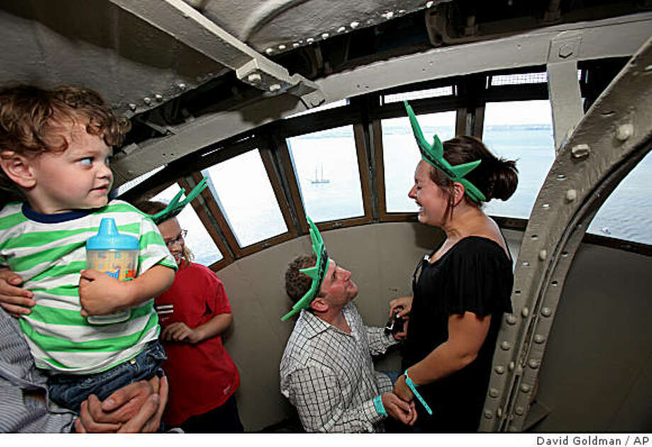 **ADDS POOL PHOTO DESIGNATION**Aaron Weisinger, 26, surprises his girlfriend Erica Breder, 25, both of Walnut Creek, Calif., with a wedding proposal while visiting the crown of the Statue of Liberty in New York, Saturday July 4, 2009. The first visitors were allowed into the Statue of Liberty's crown Saturday in nearly eight years after it was closed to the public after the Sept. 11, 2001, attacks. The base, pedestal and outdoor observation deck were reopened in 2004, but the crown remained off-limits. (AP Photos/David Goldman) Photo: David Goldman, AP