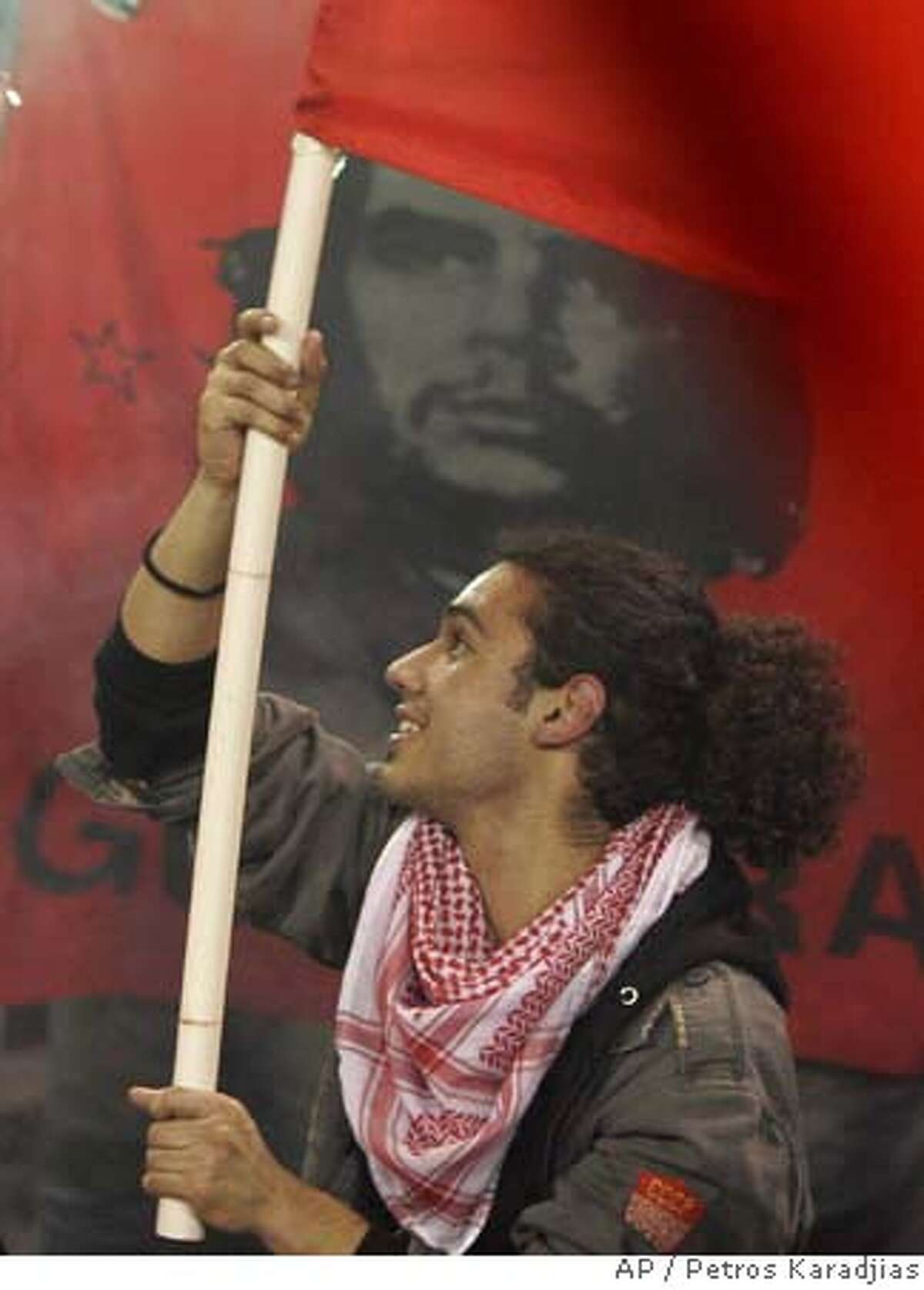 A Supporter of Communist President-elect Dimitris Christofias waves a flag in front of a Che Guevara flag during a victory rally at Eleftheria Stadium in Makedonitissa, Cyprus, Sunday, Feb. 24, 2008. Christofias won with 53.36 of the vote, against 46.64 for Conservative rival Ioannis Kasoulides, final results showed. (AP Photo/Petros Karadjias)