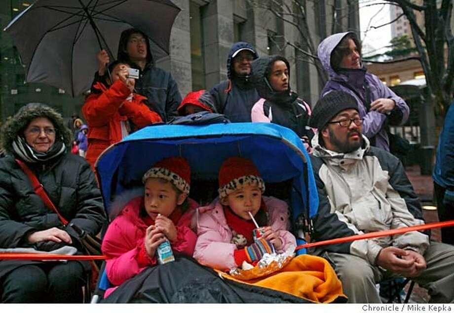 On Market Street, Hazel Chu, 6, and her sister Flossie Chu, 3, (rt) watch the Chinese New Year under the cover of their stroller on Saturday, Feb. 23, 2008 in San Francisco, Calif. Photo by Mike Kepka / San Francisco Chronicle Photo: Mike Kepka