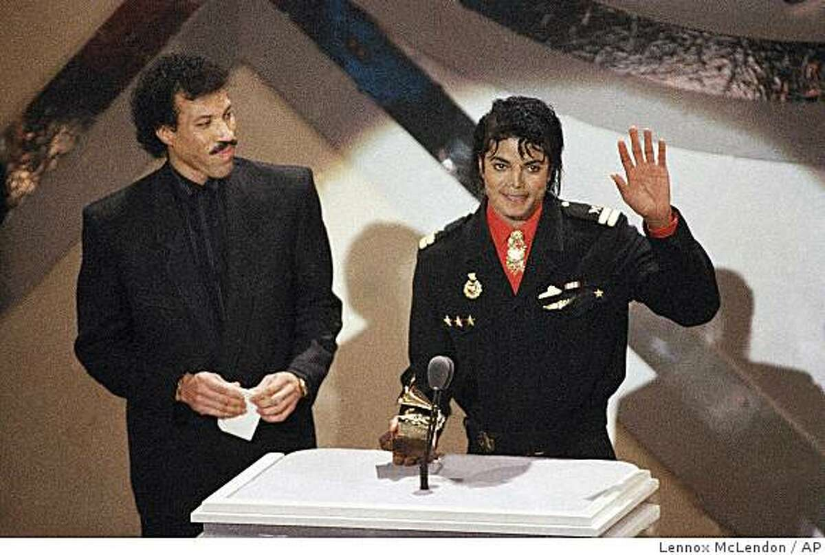 FILE - In a Tuesday, Feb. 25, 1986 file photo, Michael Jackson and Lionel Richie receive a Grammy for best song of the year for their song
