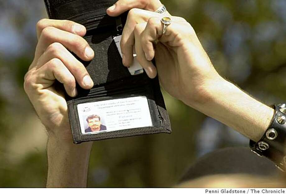 "A man holds up his ""Medical Cannabis Voluntary ID card."" Photo: Penni Gladstone, The Chronicle"