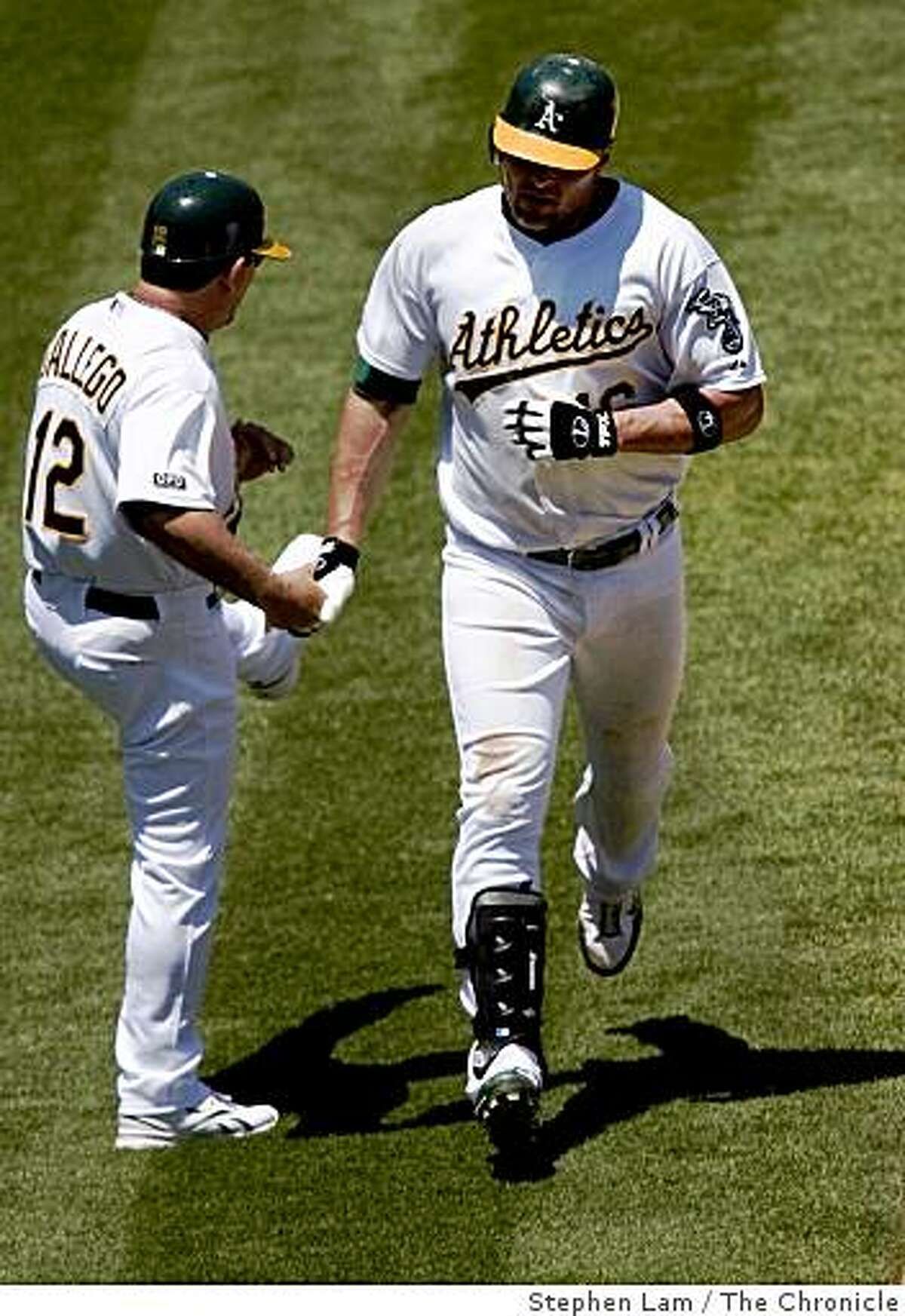 Jason Giambi (16), right, of the Oakland Athletics is being congratulated by third base coach Mike Gallego (12), left, after scoring a 2-run home run in the sixth inning against the Detroit Tigers at the Oakland-Alameda County Coliseum in Oakland, Calif. on Wednesday, July 1, 2009. The Athletics won 5-1
