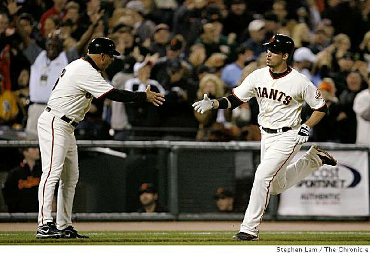 Travis Ishikawa (10) of the San Francisco Giants is being congratulated by third base coach Tim Flannery after scoring a solo home run in the eighth inning against the Texas Rangers at AT&T Park in San Francisco, Calif. on Friday June 19, 2009.