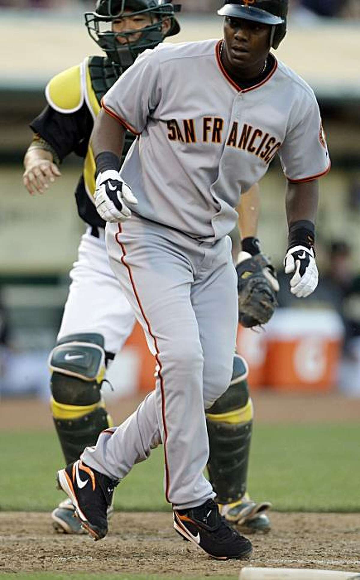 San Francisco Giants' Edgar Renteria scores in front of Oakland Athletics catcher Kurt Suzuki in the second inning of a baseball game Tuesday, June 23, 2009, in Oakland, Calif. Renteria scored on a sacrifice fly ball hit by Matt Downs. (AP Photo/Ben Margot)
