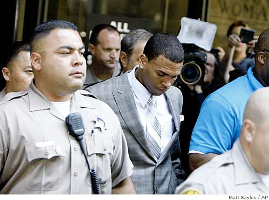 Chris Brown, center, leaves his preliminary hearing after pleading guilty to one count of felony assault on  Monday, June 22, 2009, in Los Angeles County Superior Court.  Brown was arrested in February on suspicion of hitting and threatening then-girlfriend Rihanna after a pre-Grammy party.  (AP Photo/Matt Sayles) Photo: Matt Sayles, AP
