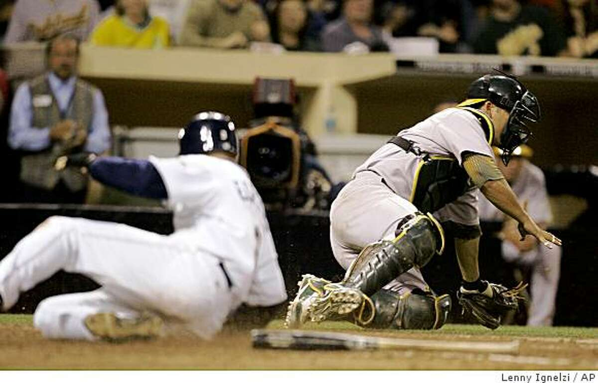 Oakland Athletics catcher Kurt Suzuki chases a wide throw as San Diego Padres' David Eckstein scores in the sixth inning of an interleague baseball game Friday, June 19, 2009 in San Diego. (AP Photo/Lenny Ignelzi)