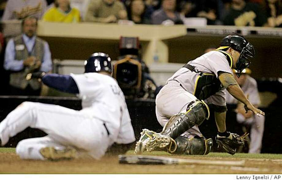 Oakland Athletics catcher Kurt Suzuki chases a wide throw as San Diego Padres'  David Eckstein scores in the sixth inning of an interleague baseball game Friday, June 19, 2009 in San Diego. (AP Photo/Lenny Ignelzi) Photo: Lenny Ignelzi, AP