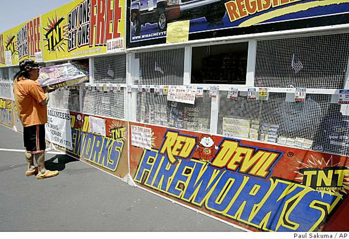 A customer looks at a box of fireworks at a fireworks booth in Newark, Calif., Wednesday, July 1, 2009, in preparation for the Fourth of July holiday weekend. (AP Photo/Paul Sakuma)
