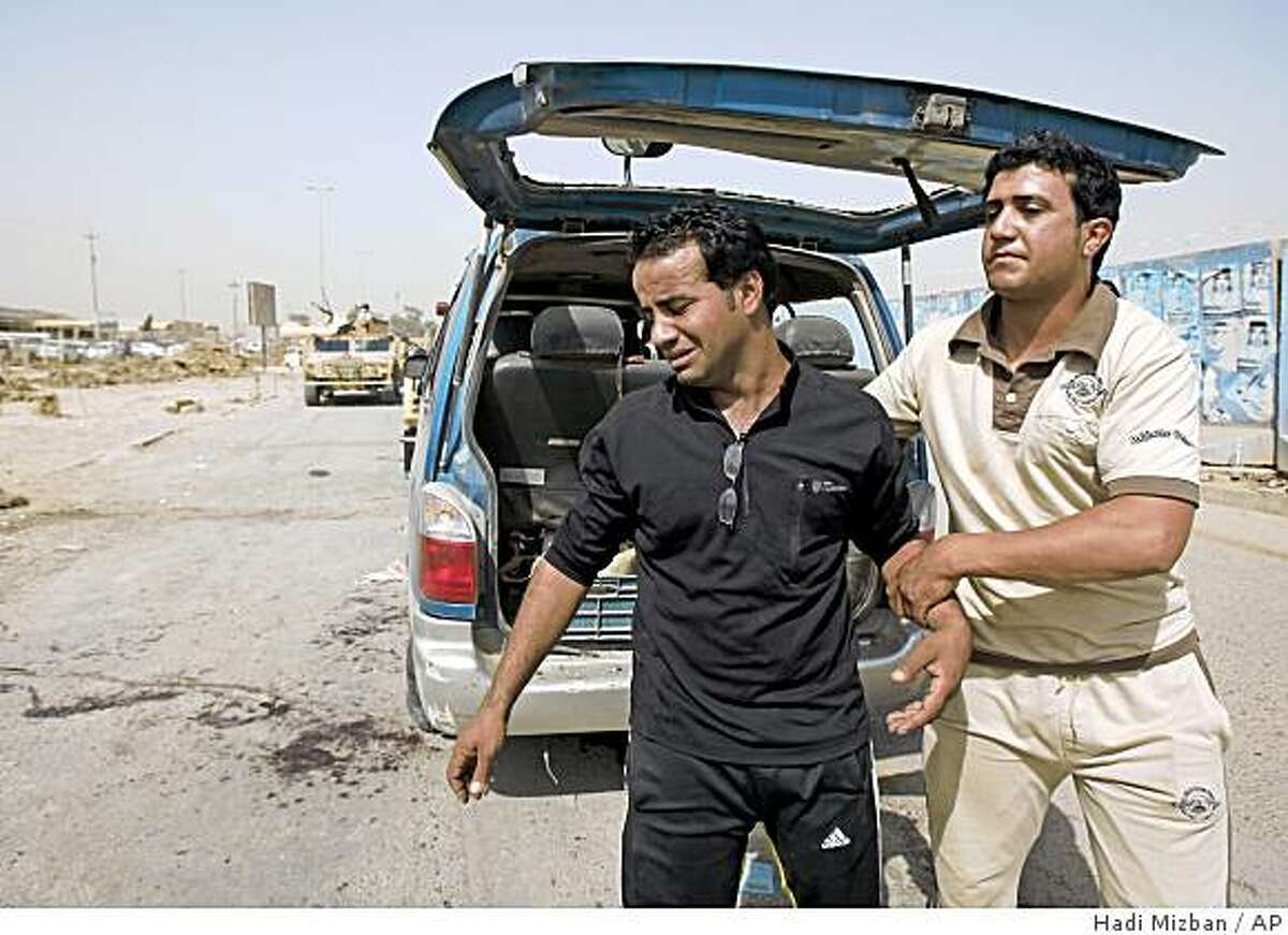 Minibus driver Abdul Kareem Hussein, left, is consoled by his brother after a roadside bombing in Baghdad, Iraq, Monday, June 22, 2009. The blast hit the bus, carrying Iraqi high school students on their way to their final exams on Monday, police said, the deadliest in a series of blasts that killed several people in Baghdad. (AP Photo/Hadi Mizban)