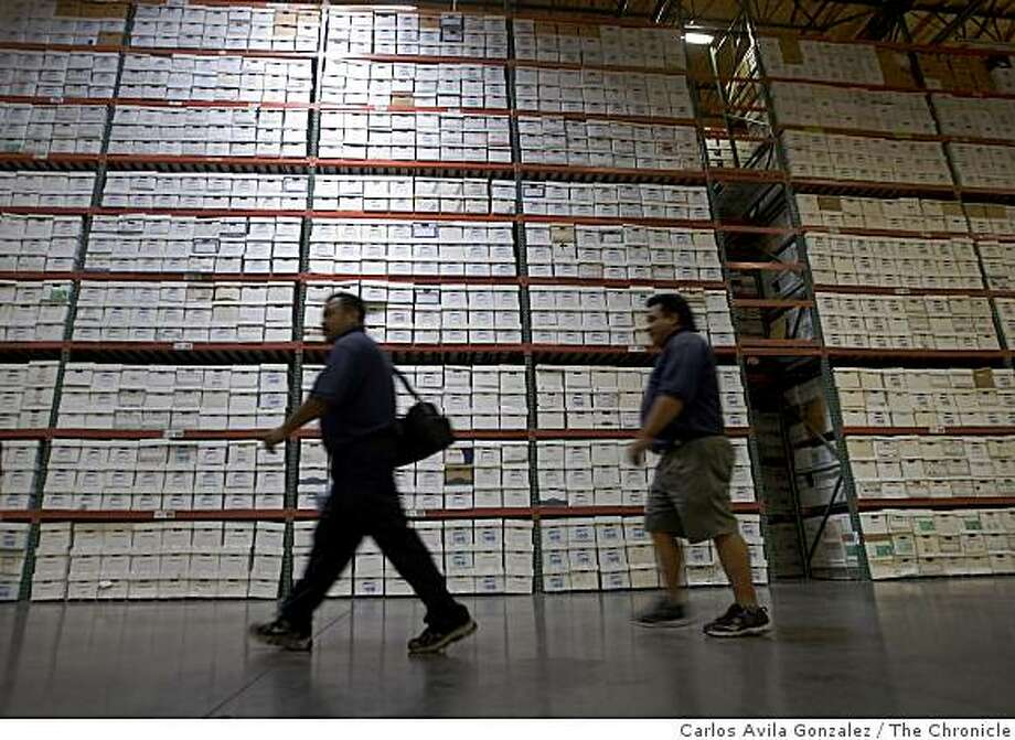 Workers walk by stacks of records at Access Information Management in Livermore, Calif., on Tuesday, June 30, 2009. The stacks of records include those abandoned by businesses that have disappeared because of the bad economy. California is on track to become the first state in the nation to have a law that allows legal disposition of abandoned personal records, which have skyrocketed as businesses have disappeared and abandoned them during the recession. Photo: Carlos Avila Gonzalez, The Chronicle