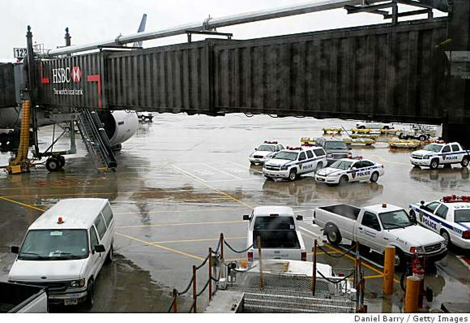 Police cars sit on the tarmac near Continental Airlines Flight 61 at Newark Liberty International Airport June 18, 2009 in Newark, New Jersey. The flight landed safely at Newark after the pilot died en route from Brussels, Belgium of natural causes, an airline spokesperson said. Photo: Daniel Barry, Getty Images