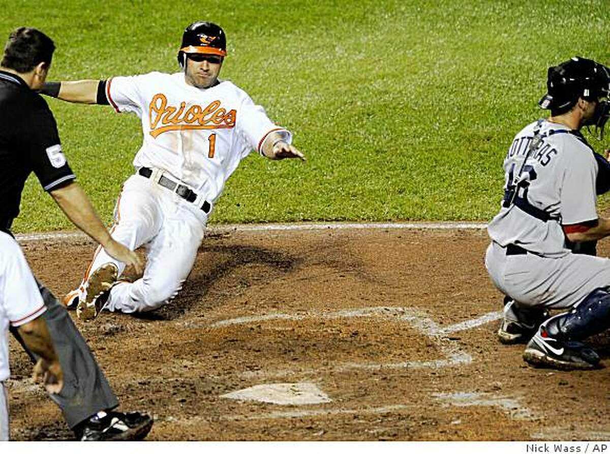 Baltimore Orioles' Brian Roberts (1) slides home to score the go-ahead run on a Nick Markakis double, next to Boston Red Sox catcher George Kattaras, right, during the eighth inning of a baseball game Tuesday, June 30, 2009, in Baltimore. Markakis went to third on the throw. The Orioles won 11-10. (AP Photo/Nick Wass)