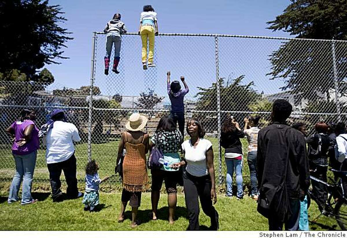 From left, Linda Williams, Valinda Willams, and Yoshika Coleham, climbs a fence in an effort to get a glimpse of First Lady Michelle Obama and California first lady Maria Shriver inside Bret Harte Elementary School in San Francisco, Calif. on Monday June 22, 2009.