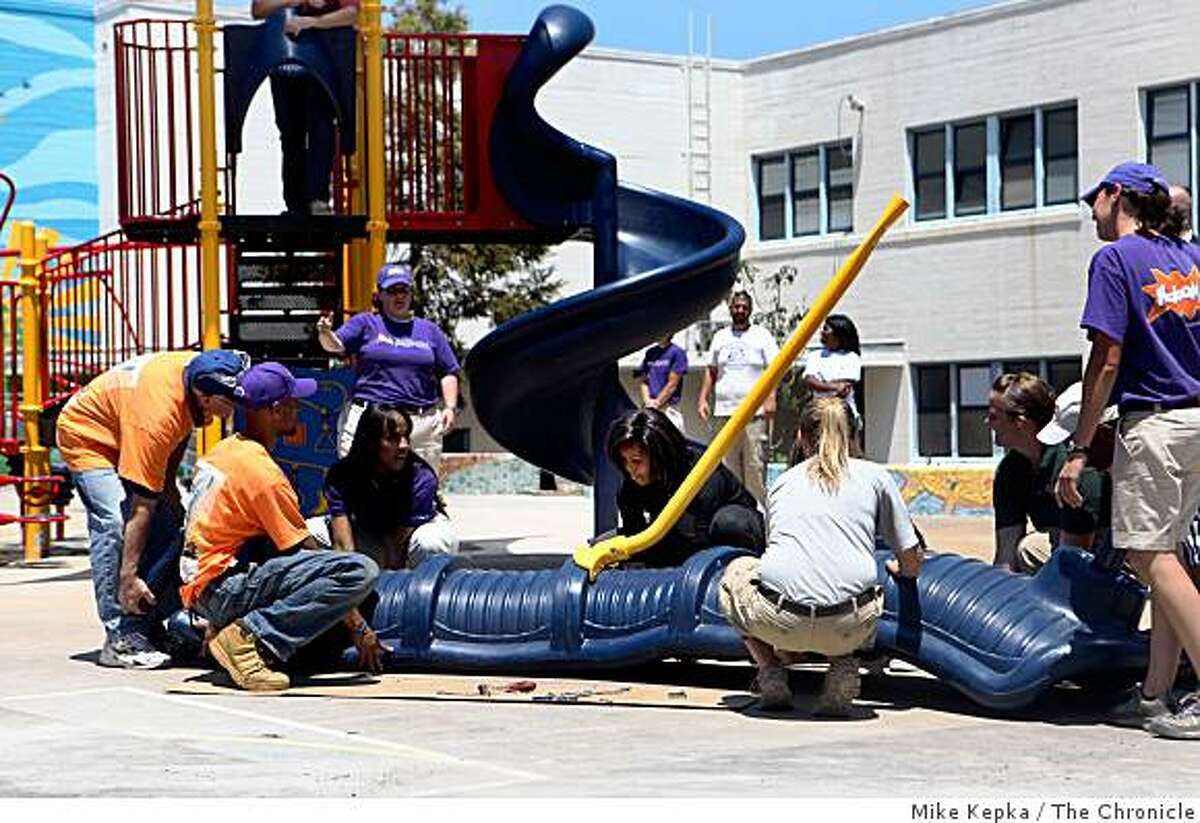 To kick start a national convention of volunteers, first lady Michelle Obama helps put the finishing touches on a playground being built at Bret Harte Elementary School in San Francisco on Monday.