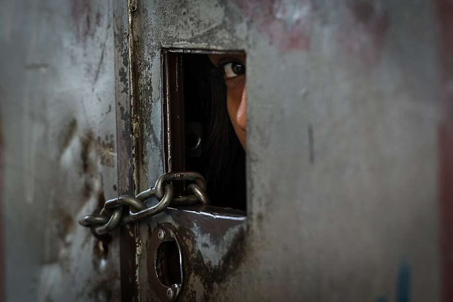 A resident looks outside from a peephole at the entrance of an ilegally occupied building before being evicted in downtown Sao Paulo, Brazil, on February 9, 2012. According to social movement group 'Frente de Luta por Moradia', FLM (Struggle for Housing Front), 75 familes out of 128 became homeless after occupying an abandoned building since last November. AFP PHOTO / Yasuyoshi CHIBA (Photo credit should read YASUYOSHI CHIBA/AFP/Getty Images) Photo: Yasuyoshi Chiba, AFP/Getty Images