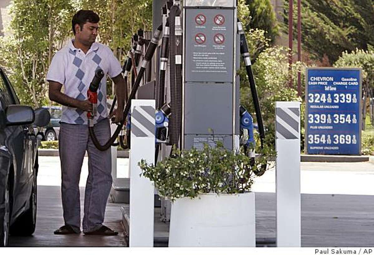 A customer pumps gas at a Chevron gas station with prices posted in background in South San Francisco, Calif., Thursday, July 2, 2009. (AP Photo/Paul Sakuma)