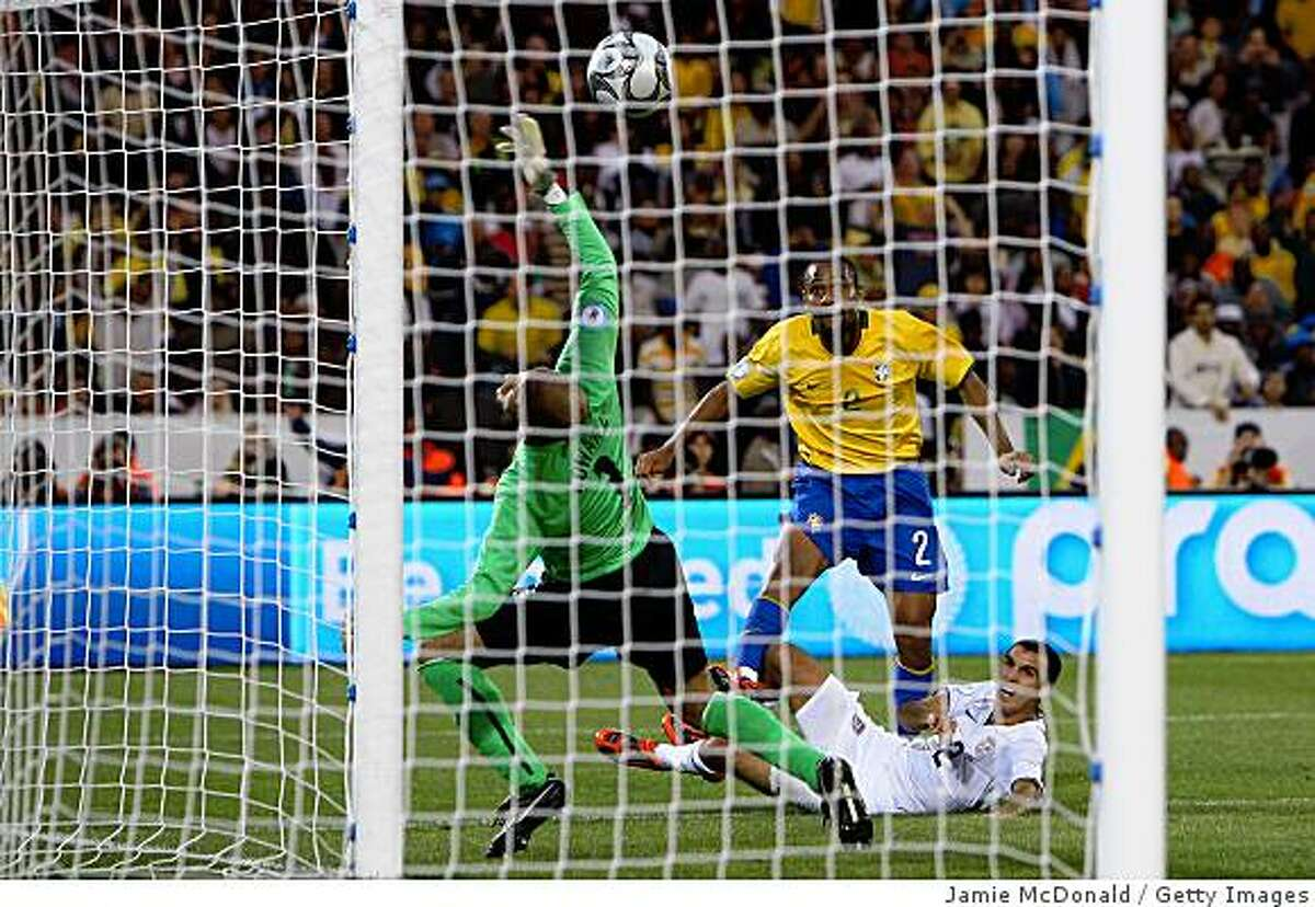 PRETORIA, SOUTH AFRICA - JUNE 18: Maicon of Brazil chips the ball over Tim Howard of USA to score the 3rd goal during the FIFA Confederations Cup match between USA and Brasil at Loftus Versfeld Stadium on June 18, 2009 in Pretoria, South Africa. (Photo by Jamie McDonald/Getty Images)