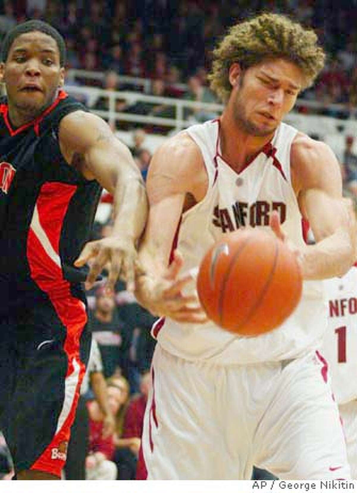 Stanford's Robin Lopez, right, and Oregon State's Calvin Hampton reach for a loose ball during the first period of a college basketball game, Saturday, Feb. 9, 2008 in Stanford, Calif. Stanford beat Oregon State 71-56. (AP Photo/George Nikitin) EFE OUT