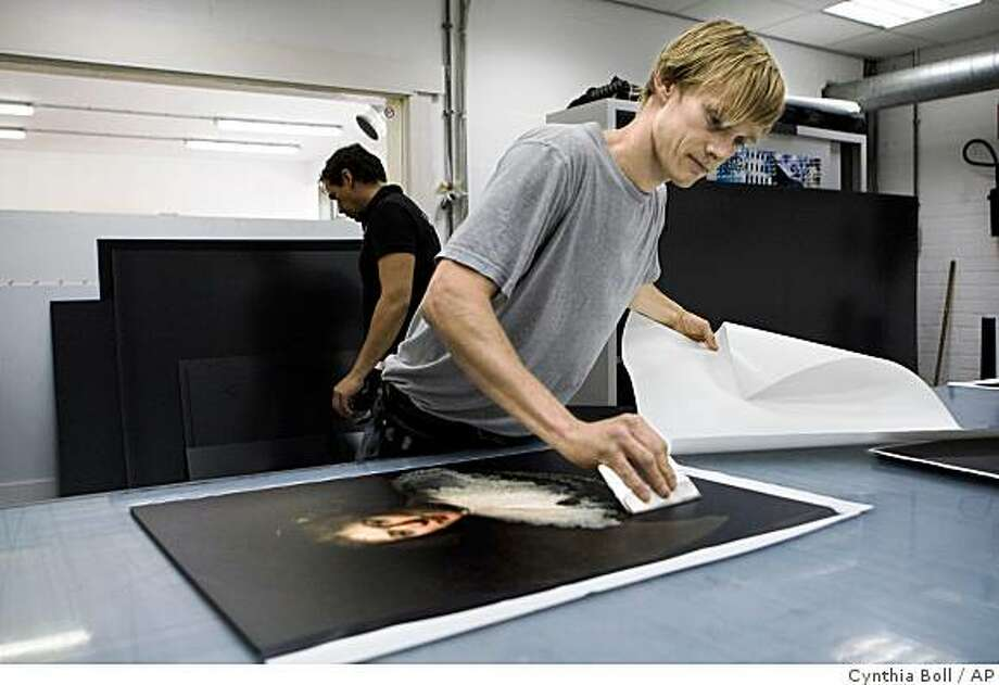 Jouke ter Hofstede of the Van Straaten printing company mounts digital images onto boards to prepare them for an exhibit of images of all paintings by Rembrandt in Boesingheliede, Netherlands, Thursday, June 25, 2009. The images will be displayed at an exhibition of images of all 317 known paintings, 285 etchings and more than 100 drawings by Rembrandt in Amsterdam. The artworks are being reproduced in their true size and have been digitally enhanced by one of the world's leading Rembrandt experts, Ernst van de Wetering, to restore the color and detail they had when they left Rembrandt's studio nearly 400 years ago. The exhibition will start at July 5. (AP Photo/Cynthia Boll) Photo: Cynthia Boll, AP