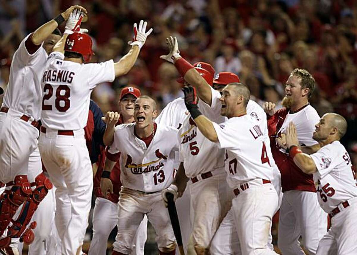 St. Louis Cardinals greet teammate Colby Rasmus (28) at home plate after Rasmus hit a walk-off home run to defeat the San Francisco Giants 2-1 in the 10th inning of a baseball game Wednesday, July 1, 2009, in St. Louis. (AP Photo/Jeff Roberson)