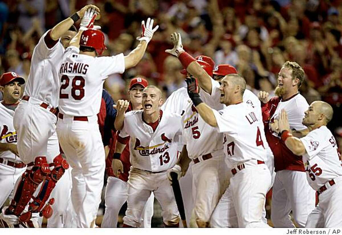 St. Louis Cardinals greet teammate Colby Rasmus (28) at home plate after Rasmus hit a walk-off home run to defeat the San Francisco Giants 2-1 in the 10th inning of a baseball game Wednesday, July 1, 2009, in St. Louis.