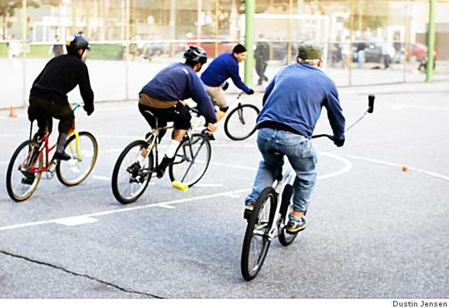 Players play bike polo on a hard court. Photo: Dustin Jensen