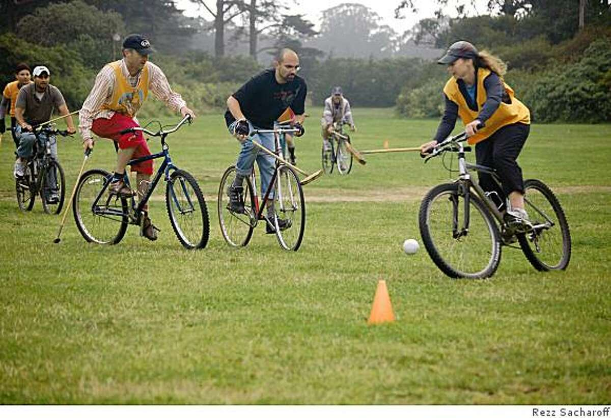 Players playing bike polo on the grass at Golden Gate Park.