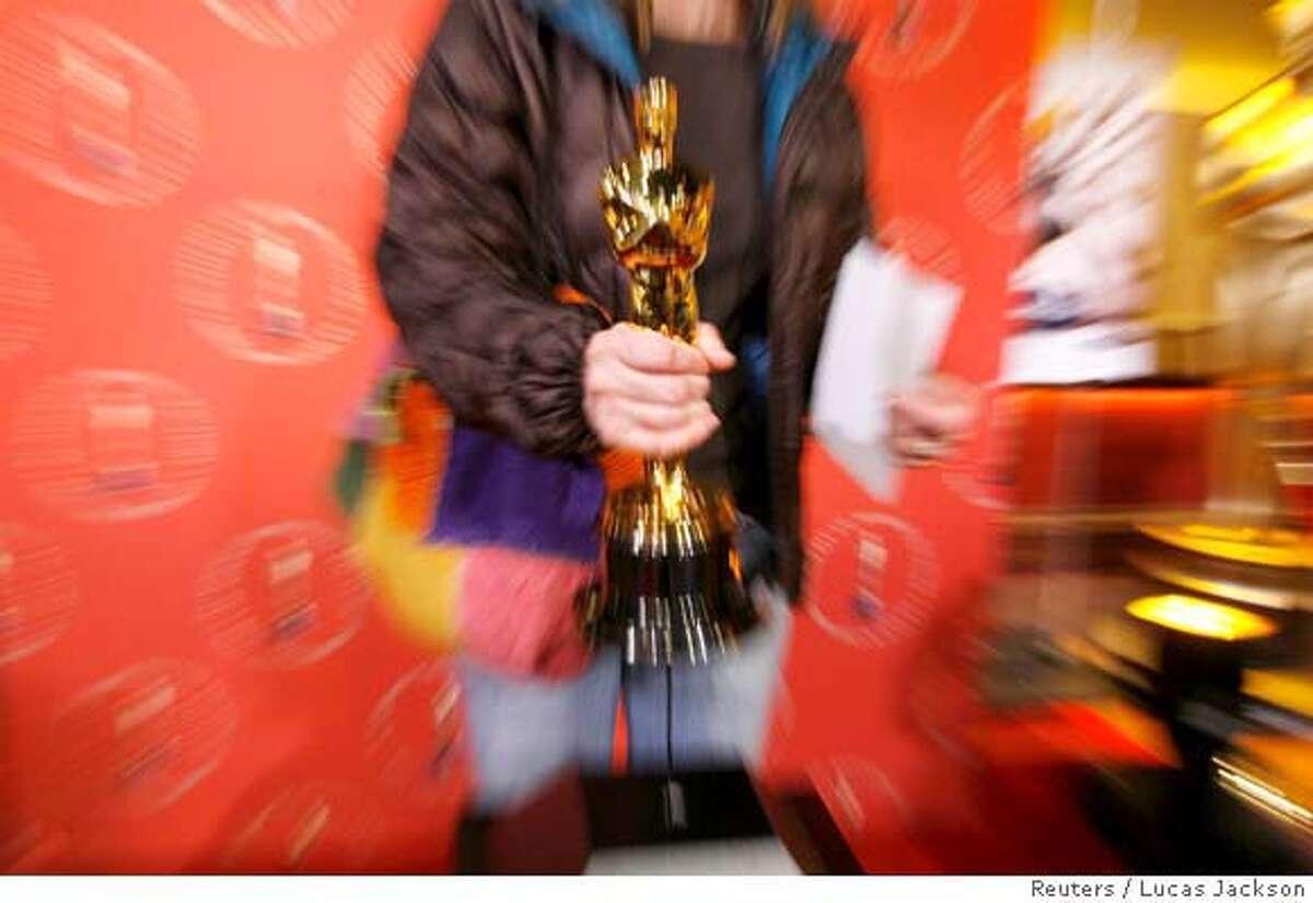 A tourist lifts an Oscar statuette at a