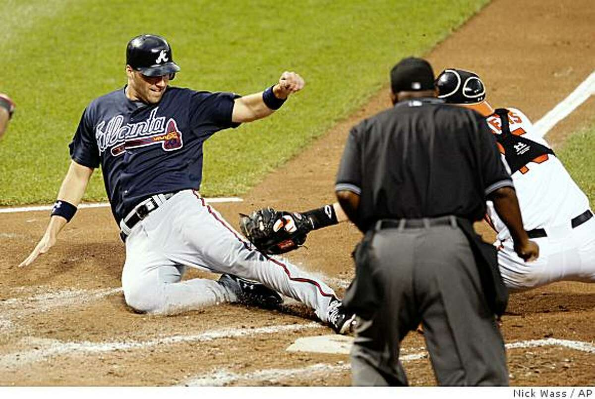 Baltimore Orioles catcher Matt Wieters, right, tags out Atlanta Braves' Jeff Francoeur, left, out at the plate during the fourth inning of a baseball game, Saturday, June 13, 2009, in Baltimore. Francoeur was trying to score on a single by teammate Nate McLouth. (AP Photo/Nick Wass)